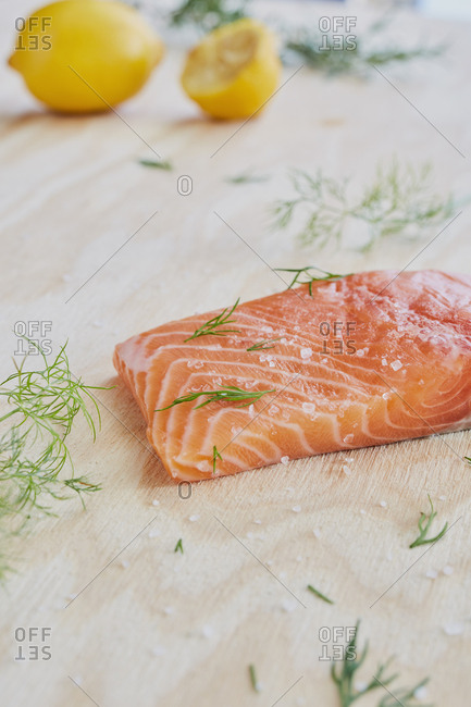 Close-up of seasoned salmon slice and rosemary on table