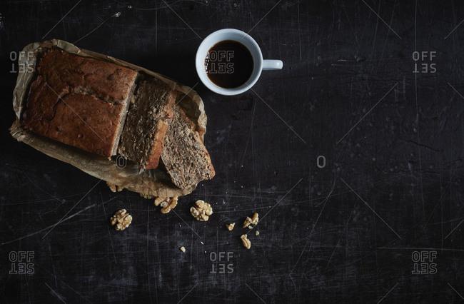 Directly above shot of walnut cake with coffee mug on granite