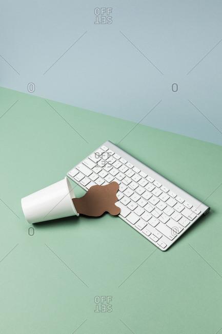 Spilt coffee art on wireless keyboard at green table