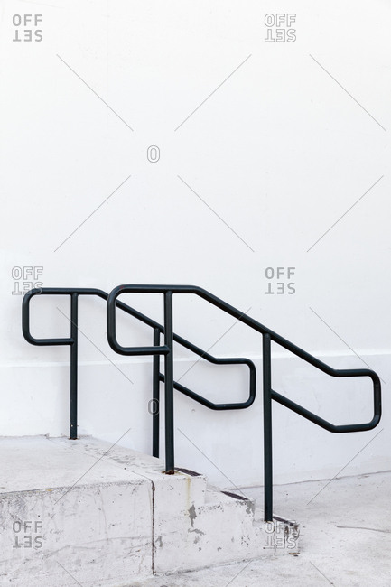 Black railing on steps by white wall