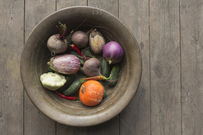 Directly above shot of various vegetables in container on wooden table
