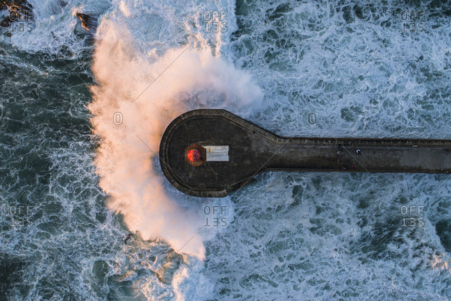 Directly above view of wave splashing on pier in sea, Porto, Portugal