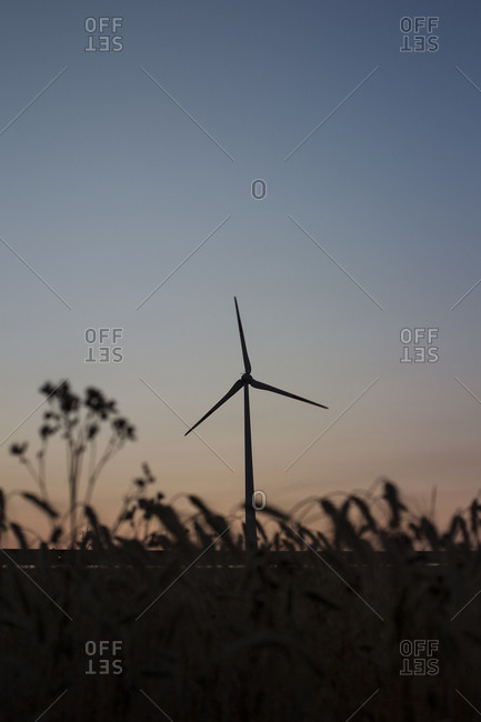 Wind turbine silhouetted at sunset