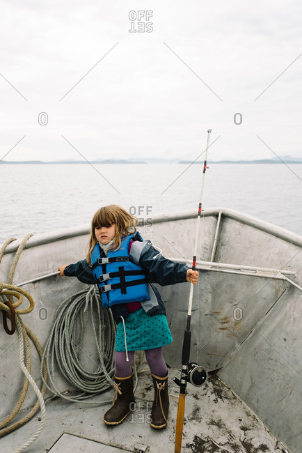 Little girls standing on a boat with a fishing pole