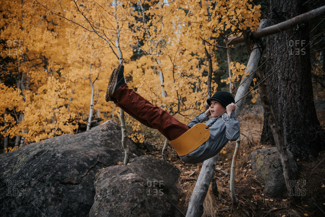 Boy swinging on a swing set during fall