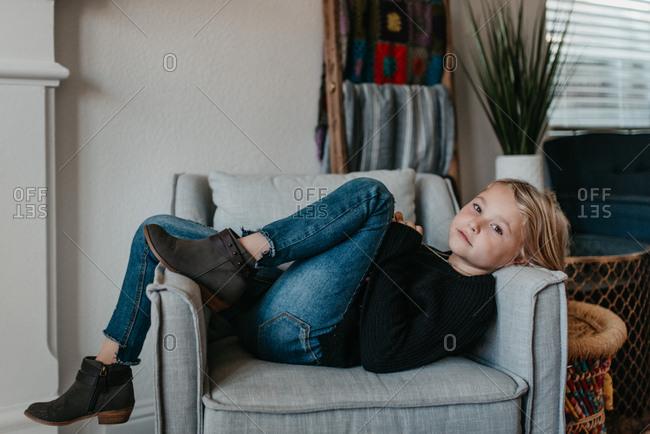 Little girl lying on armchair