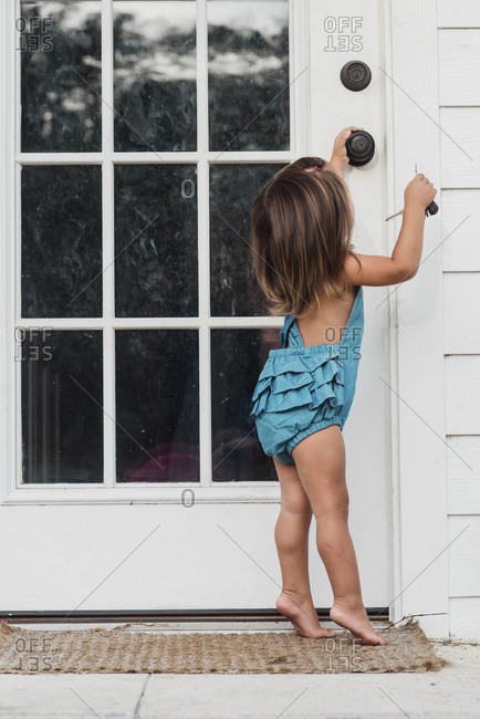 Toddler girl opening door with keys