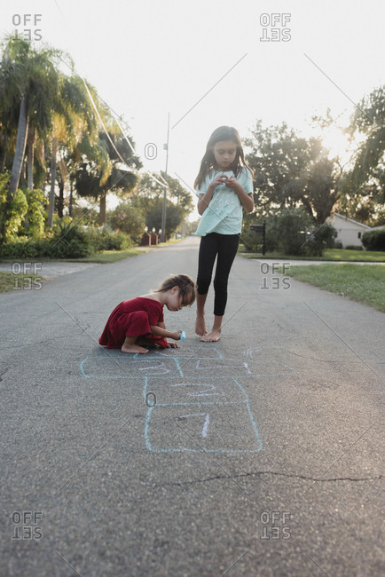Two sisters playing in road with chalk
