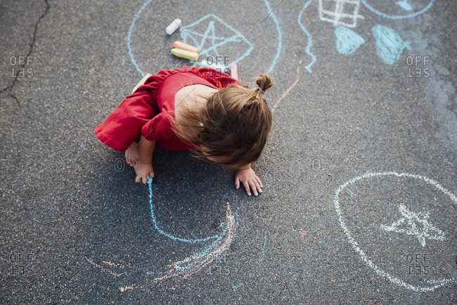 Toddler girl playing with chalk in road