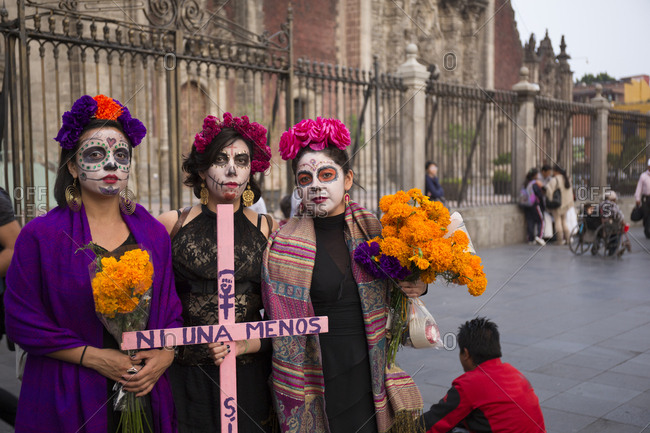 Mexico City, Mexico - November 1, 2017: Women dressed in costume and holding cross at the Day of the dead celebrations at Zocalo square