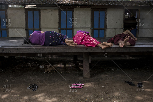 Bagan, Myanmar - September 26, 2016: People sleeping on a platform in the streets of Bagan