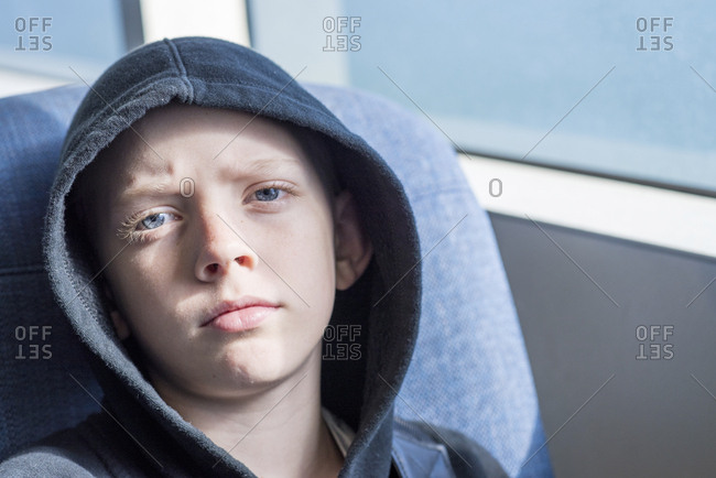 Close-up portrait of confident boy wearing hooded shirt in bus