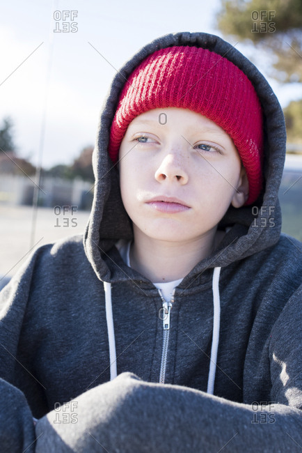Thoughtful boy wearing knit hat and hooded shirt while looking away