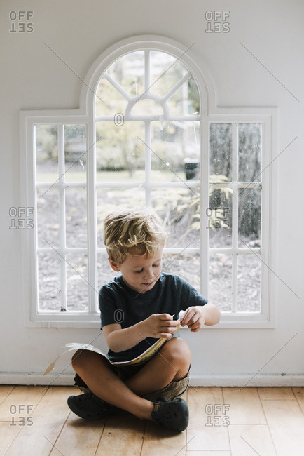 Boy with book sitting on floor against window at home