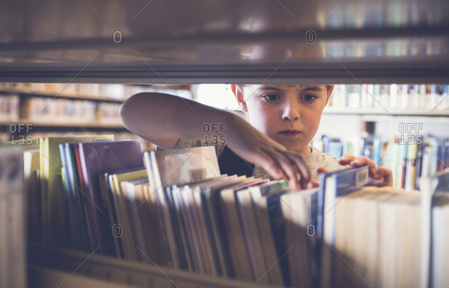 Serious boy searching for book from shelf at library