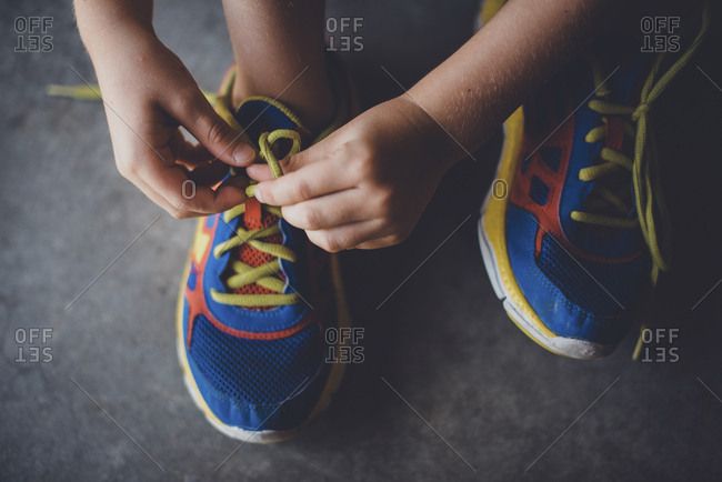 Cropped hands of boy tying shoelace