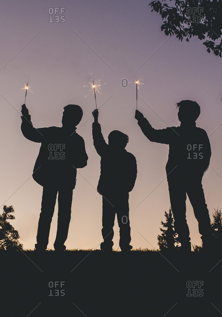 Silhouette brothers holding sparklers against clear sky during dusk
