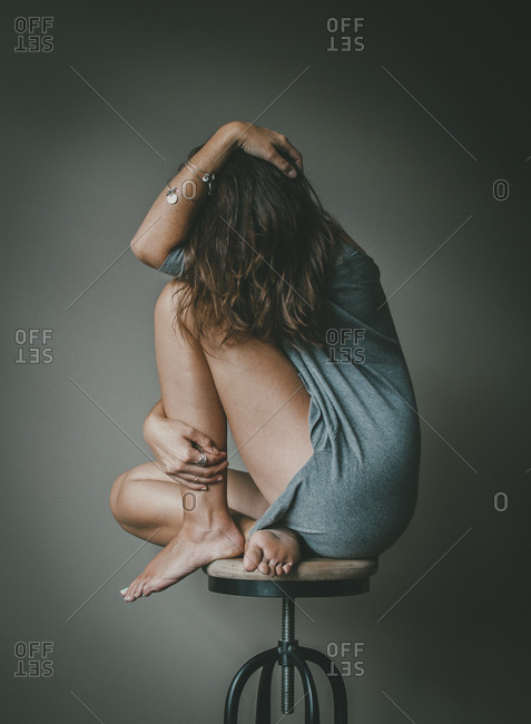 Full length of depressed woman with obscured face sitting on stool against wall