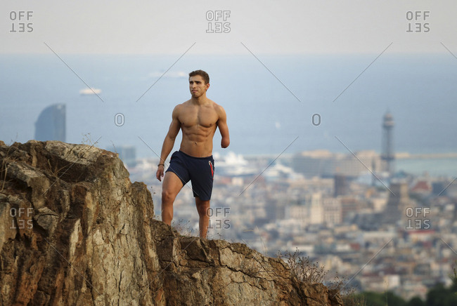 Physically challenged shirtless man looking away while standing on cliff against cityscape