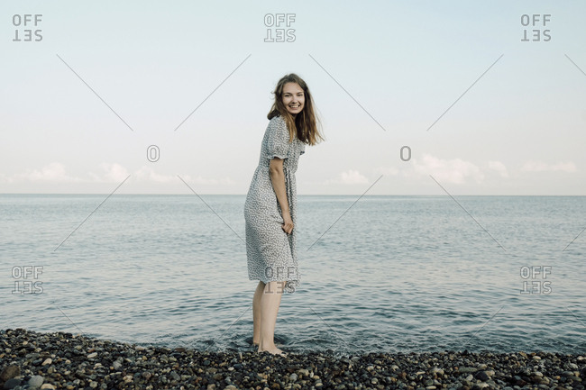 Portrait of cheerful woman standing in river against sky