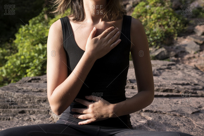 Midsection of woman mediating while touching chest and abdomen during sunny day