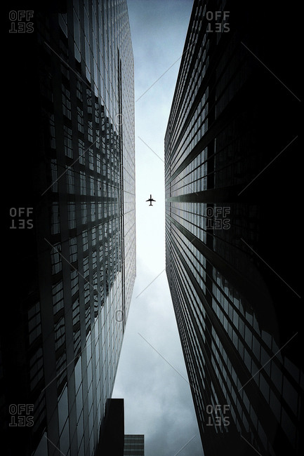 Directly below shot of airplane flying over buildings in city