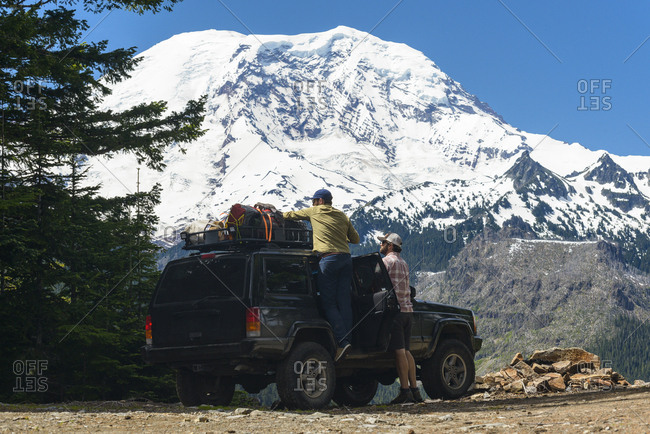 Hiker adjusting luggage on off-road vehicle by friend against snowcapped mountains