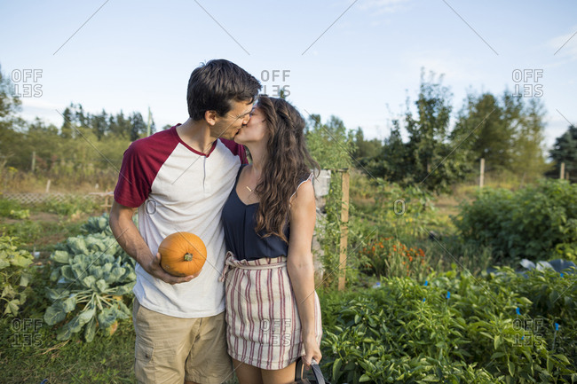 Young couple kissing while standing against sky at community garden