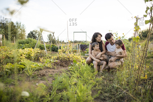 Family on field against clear sky at community garden