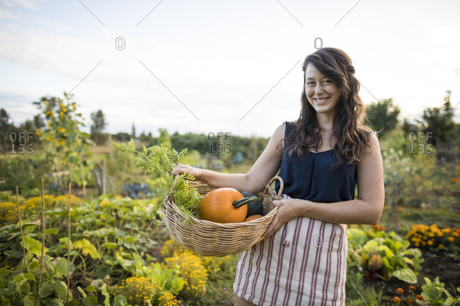 Portrait of cheerful woman carrying vegetables in basket against clear sky at community garden