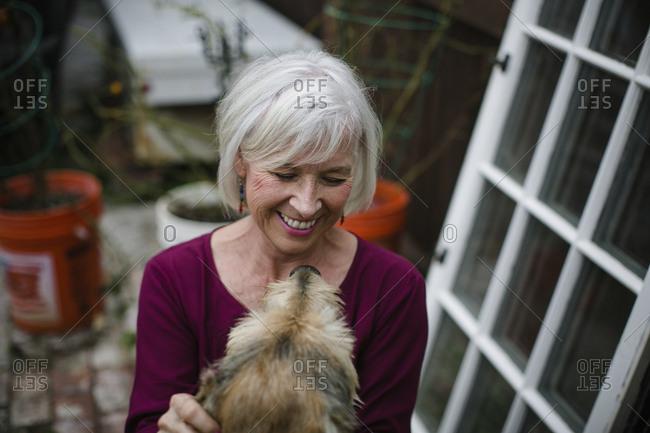 High angle view of cheerful senior woman with dog at yard