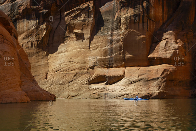 Hiker kayaking on Lake Powell against canyons