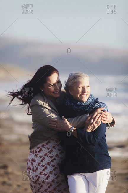 Cheerful daughter embracing mother at beach during sunny day