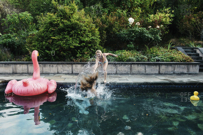 Playful teenage girl pushing friend into swimming pool