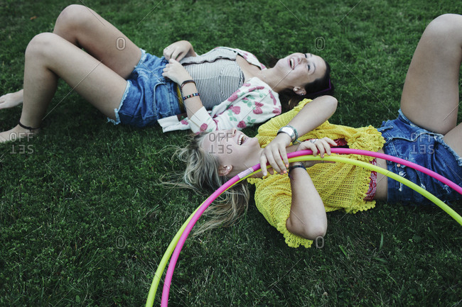 High angle view of cheerful female friends lying on grassy field with plastic hoops at park