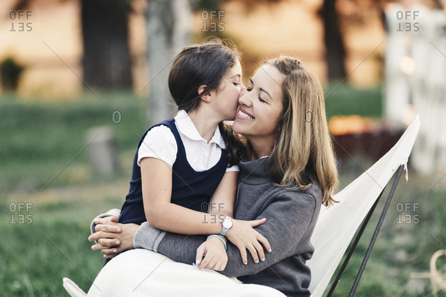 Daughter wearing school uniform while kissing mother at yard