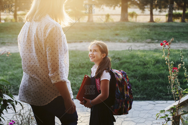 Daughter wearing school uniform while looking at mother