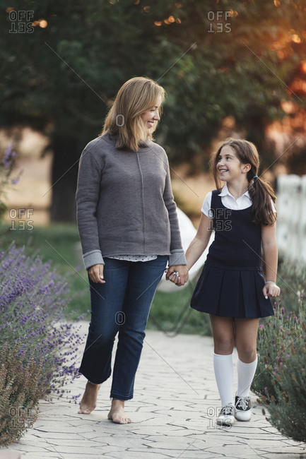 Happy mother and daughter holding hands while walking at yard
