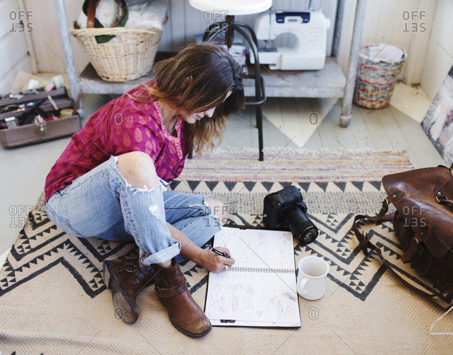 High angle view of woman writing on diary while sitting on rug in office