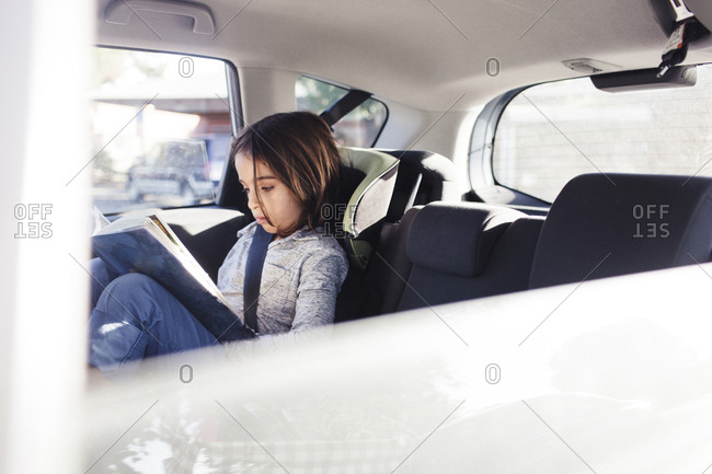 Serious boy reading book while sitting in car seen through window