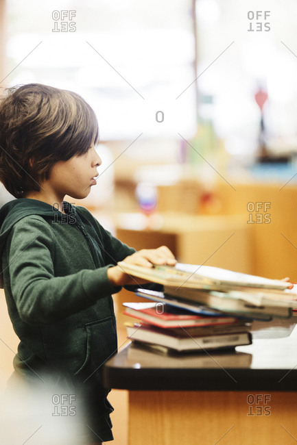 Boy with books at checkout in library