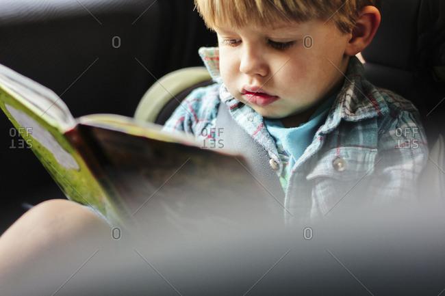 Cute boy reading book in car