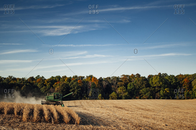 Combine harvester on field against cloudy sky