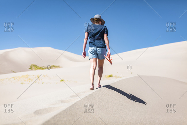 Rear view of woman holding flip-flop while walking on sand at Great Sand Dunes National Park during sunny day
