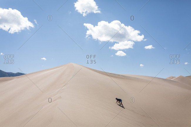 High angle view of woman climbing sand dune at national park during sunny day