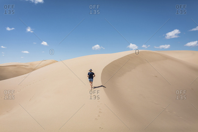 High angle view of woman walking on sand at Great Sand Dunes National Park during sunny day