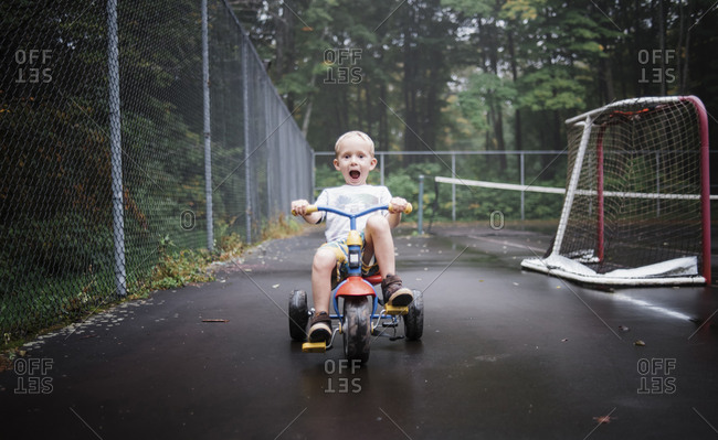 Portrait of playful boy riding tricycle at playground