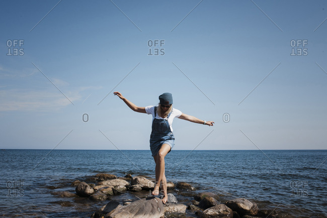 Woman with arms outstretched walking on rocks against sea and sky