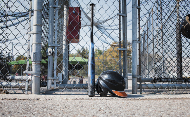 Baseball bat and sports helmet against chain-link fence at playing field during sunny day