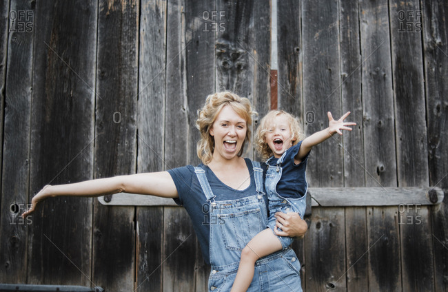 Portrait of cheerful mother and daughter with arms outstretched against old barn